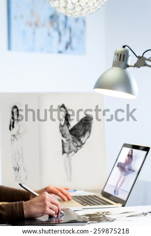 Extreme close up of Fashion designer working on new collection in studio. - stock photo