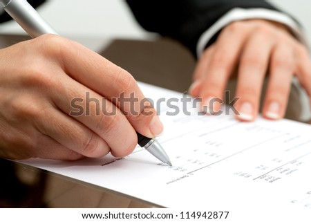 Extreme close up of female hand pointing with pen on accounting document.