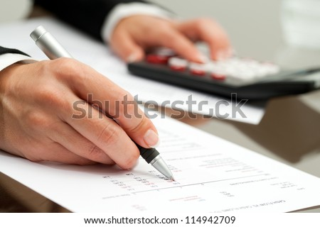 Extreme close up of female hand with pen pointing on cash flow document.