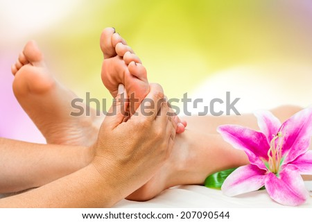 Extreme close up of female Spa therapist doing foot massage. - stock photo