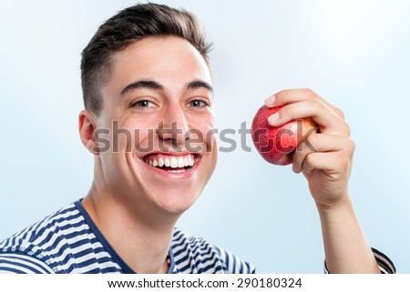 Extreme close up of Handsome young teen holding red apple and  showing healthy teeth.   - stock photo