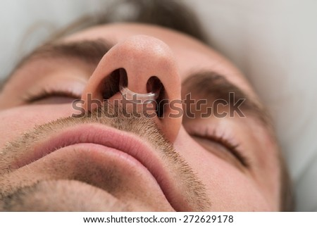 Extreme Close-up Of Man Face With Nose Clip Device - stock photo