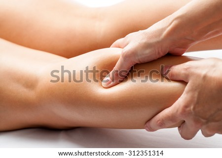 Extreme close up of osteopath applying pressure with thumb on female calf muscle.