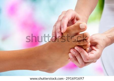 Cực cận của vật lý trị liệu làm massage bấm huyệt vào bóng đá nữ.  nền đầy màu sắc.