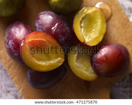 Extreme close up of plums with honey served on wooden board