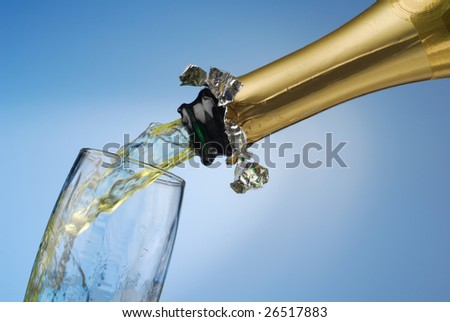 Extreme close-up of pouring champagne in to glass - stock photo
