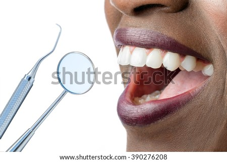 Extreme close up of smiling African female mouth showing white teeth.Hatchet and mouth mirror isolated on white background. - stock photo