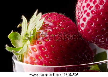 Extreme close up of strawberries in glass on black background - stock photo