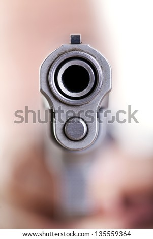 Extreme close up of the dangerous front edge of a 9mm handgun. Even though the depth of field is extremely shallow, an obscured shape of a head and hands holding the gun can be seen in the background. - stock photo