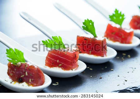 Extreme close up of tuna appetizers on ceramic spoons for catering. - stock photo