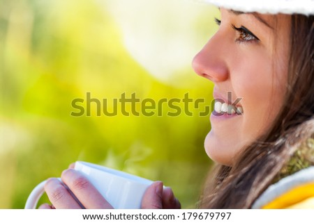 Extreme close up of young girl drinking coffee outdoors.