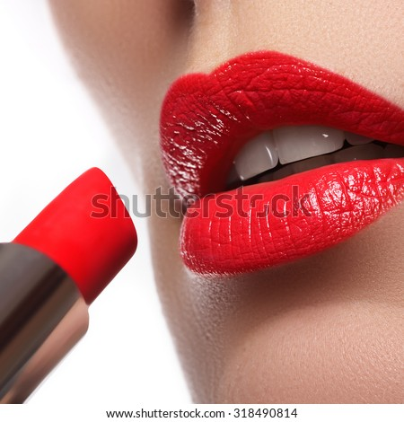 Extreme close up on model  applying red lipstick. Makeup. Professional fashion retro make-up. Red lipstick.  - stock photo