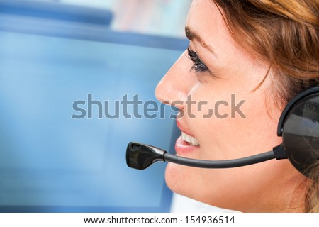Extreme close up portrait of female with headset giving customer service. - stock photo