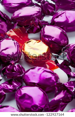 Extreme close-up shot of purple candies surrounding a golden hard candy. - stock photo