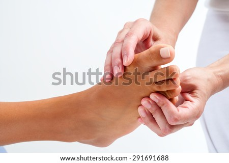 Extreme close up Therapist doing reflexology massage on human female foot. Isolated on white background. - stock photo