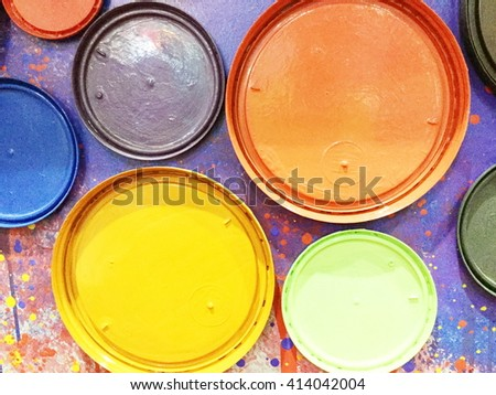 Extreme closeup colorful paint cans lid on a wall - stock photo