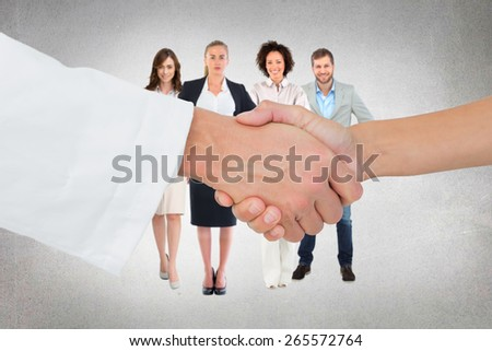 Extreme closeup of a doctor and patient shaking hands against grey room - stock photo