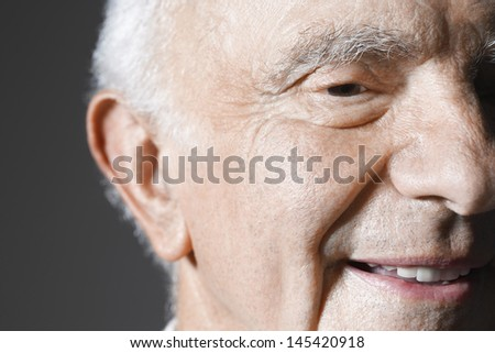 Extreme closeup of a smiling senior man against gray background - stock photo