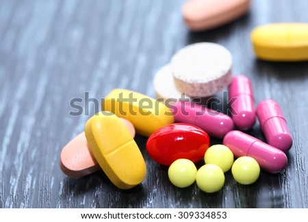 Extreme closeup of various colored pills on dark board