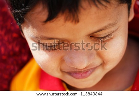 Extreme closeup photo of handsome young but shy indian/asian boy(child) smiling and happy with himself. The kid in the photo is about 6 years old student of elementary school - stock photo