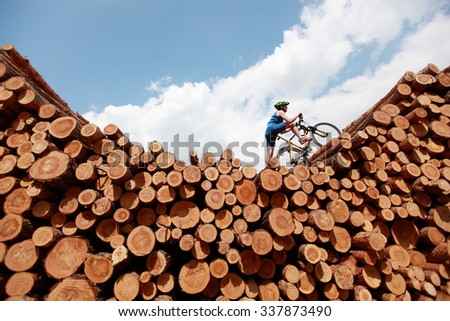 extreme cycling - fit man with his bicycle on top of large pile of logs - stock photo