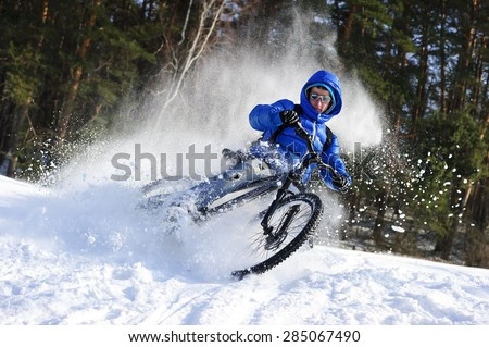 Extreme cycling - rider on mountain bike in snow winter forest  - stock photo