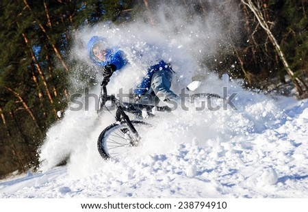 Extreme cyclist riding on mountain bike in winter forest - stock photo