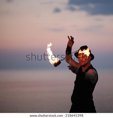 Extreme fire dance; portrait of showman outside - stock photo