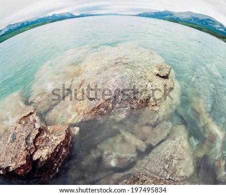 Extreme fisheye wide angle view of Tagish Lake water surface landscape, Yukon Territory, Canada - stock photo