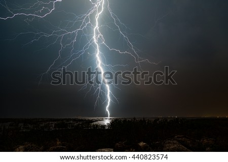 Extreme lightning strike over water at night. - stock photo