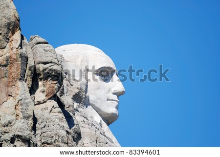 Extreme side view of Mount Rushmore showing only the head of George Washington ... white against bright blue sky. - stock photo