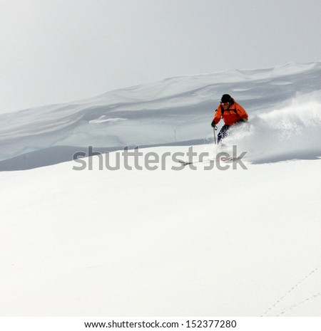 Extreme skier in deep powder under a large cornice, Utah, USA. - stock photo