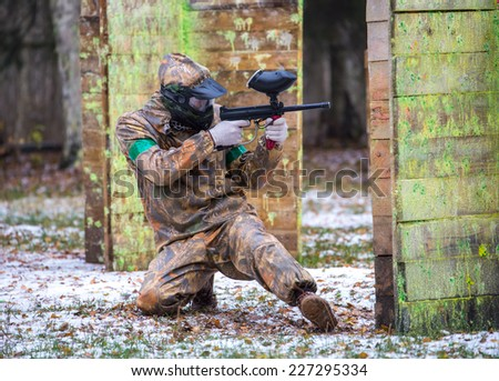 Extreme sportsman playing paintball game on first snow - stock photo