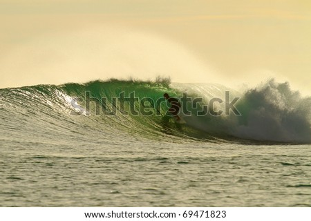 Extreme surfer on perfect golden wave - stock photo