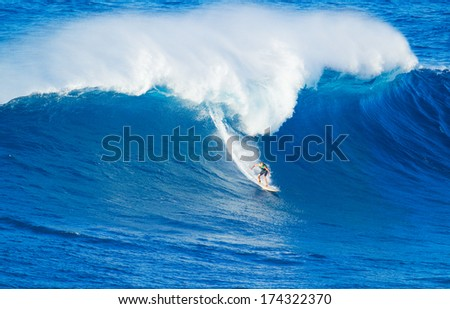 Extreme surfer riding giant ocean wave in Hawaii - stock photo