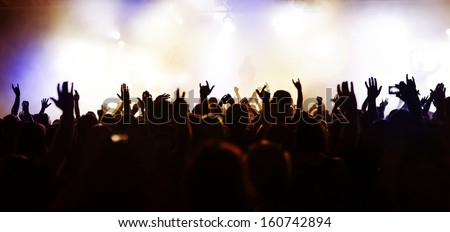 extreme wide-angle/panorama photo of a concert crowd in front of bright stage lights - stock photo
