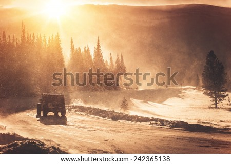 Extreme Winter Road Condition. Colorado Mountain Road and the Winter Storm with High Wind. All Wheels Drive SUV on the Icy Road Covered by Snow. - stock photo