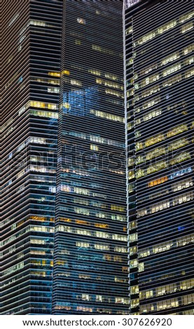 Extreme zoom shot of these urban sky scrapers at night, reveals their simplistic and angular architectural style. - stock photo