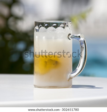 Extremely cold glass with beer on a table in a very hot summer day. Image with clipping path.  - stock photo