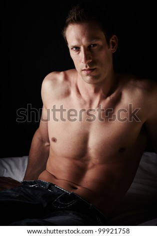 Extremely fit and handsome young caucasian adult man sitting on a bed against a dark wall wearing blue jeans and without a shirt.. - stock photo