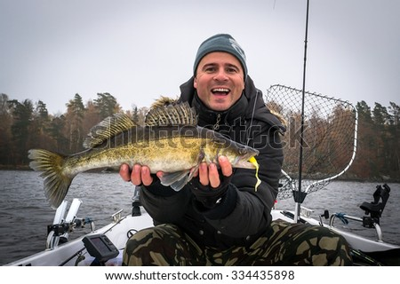 Extremely happy angler with autumn walleye fish - stock photo
