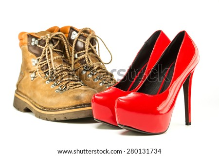 Extremes meet: mens working or hiking boots in a vintage look and in contrast to them a pair of shiny fancy red high heels shoes with inner platform and stiletto.  - stock photo