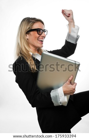 Exultant attractive blond businesswoman wearing glasses cheering and celebrating a success as she holds her laptop under her arm, side view isolated on white - stock photo