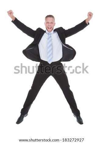 Exultant stylish young businessman in a suit jumping and raising his fists in the air as he celebrates a success full length isolated on white