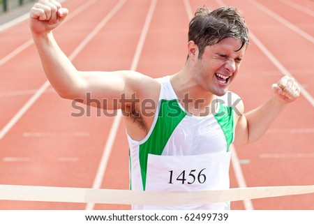 Exulting sprinter showing expression of victory in front of the arrival line in a stadium - stock photo