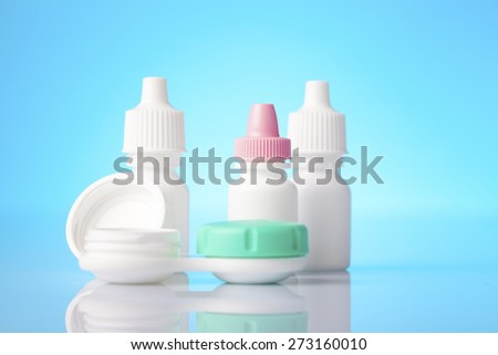 Eye and allergy treatment and eye lenses in a case on blue background - stock photo