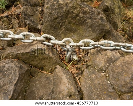 Eye bolt with iron chain anchored into sandstone rock. Twisted chain of climber safety path fixed in block by screws snap hooks. - stock photo