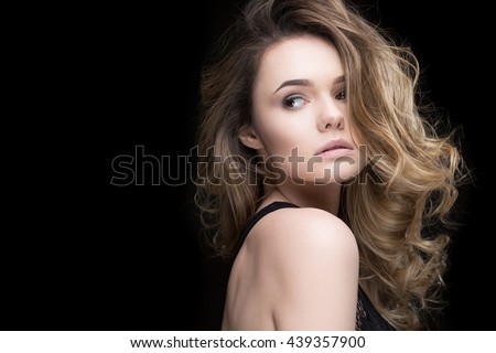 Eye catching girl. Gorgeous curly haired young woman looking sensually over her shoulder copyspace on the side - stock photo