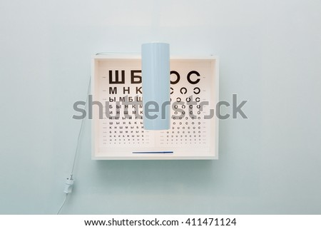 Eye chart with cyrillic letters in ophtalmology cabinet  - stock photo
