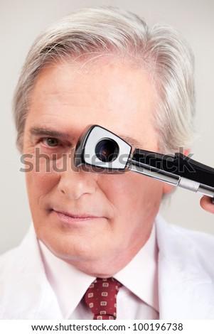 Eye doctor optometrist with opthalmoscope. - stock photo